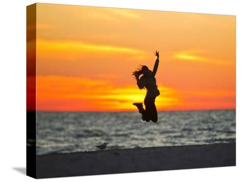 Silhouette of a Woman Jumping in Front of a Colorful Beach Sunset-Mike Theiss-Stretched Canvas Print