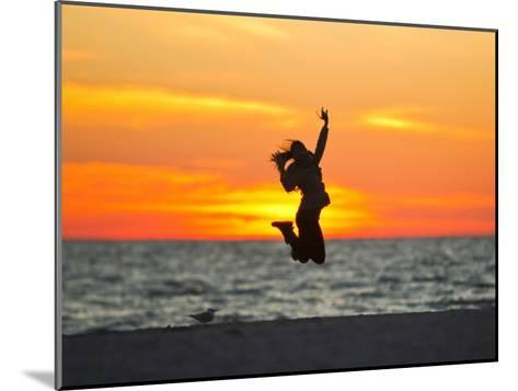 Silhouette of a Woman Jumping in Front of a Colorful Beach Sunset-Mike Theiss-Mounted Photographic Print