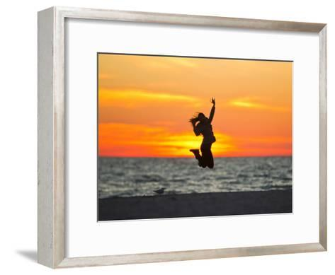 Silhouette of a Woman Jumping in Front of a Colorful Beach Sunset-Mike Theiss-Framed Art Print