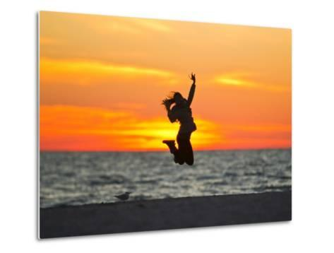 Silhouette of a Woman Jumping in Front of a Colorful Beach Sunset-Mike Theiss-Metal Print