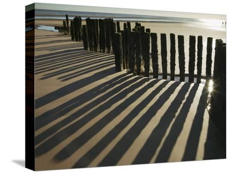 Silhouette of the Remains of a Groyne on the Beach at Dawlish Warren-Nigel Hicks-Stretched Canvas Print