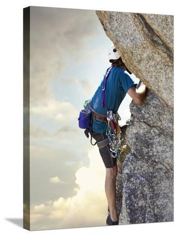 Young man rock climbing up a vertical cliff--Stretched Canvas Print