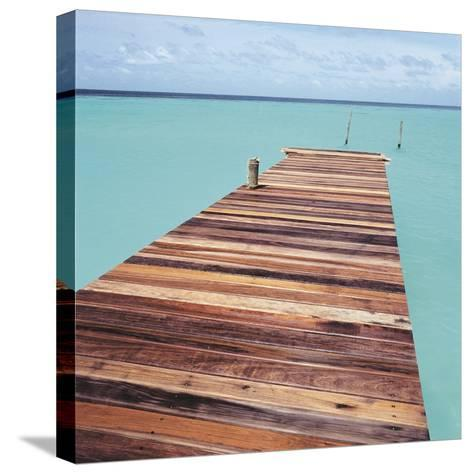 Wooden jetty leading out to sea--Stretched Canvas Print