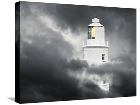 Lighthouse Emerging From Dark Clouds-Paul Hardy-Stretched Canvas Print