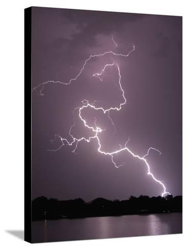 Lightning Striking Ground Near Residential Lake-Jim Reed-Stretched Canvas Print
