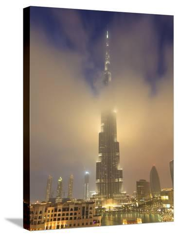 Burj Khalifa Illuminates the Clouds and Surrounding Skyline at Night, Downtown, Dubai, Uae-Amanda Hall-Stretched Canvas Print