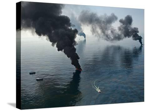 Smoke rises from surface oil being burned by cleanup crews.-Joel Sartore-Stretched Canvas Print