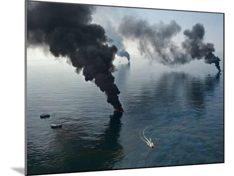 Smoke rises from surface oil being burned by cleanup crews.-Joel Sartore-Mounted Photographic Print