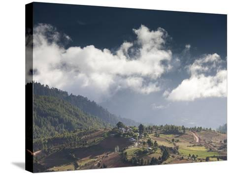Village of Shingyer Against a Dramatic Backdrop of Mountains and Clouds, Phobjikha Valley, Bhutan, -Lee Frost-Stretched Canvas Print