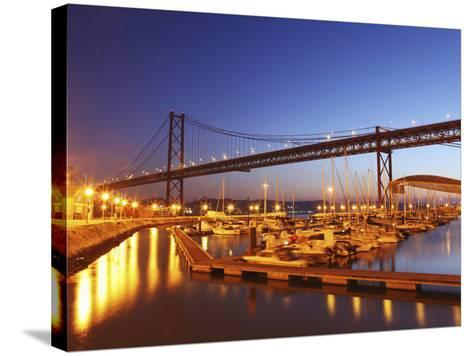 Boats on the River Tagus Move at Night in the Doca De Santa Amaro Marina under the 25 April Bridge,-Stuart Forster-Stretched Canvas Print
