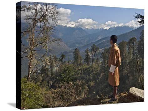 A Bhutanese Man in National Costume Views an Eastern Himalayan Mountain Range from the 11,000-Foot--Nigel Pavitt-Stretched Canvas Print