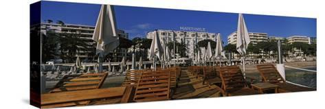 Lounge Chairs and Beach Umbrellas on the Beach, Cannes, Alpes-Maritimes, Provence-Alpes-Cote D'A...--Stretched Canvas Print