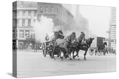 A Team of Horses Pulls a Steam Pumper across Paved Streets Toward a Fire Scene.--Stretched Canvas Print