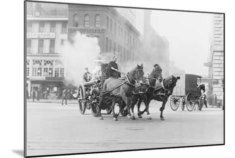 A Team of Horses Pulls a Steam Pumper across Paved Streets Toward a Fire Scene.--Mounted Art Print