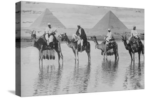 Camels with Native Riders on Board Stand in Reflective Floodwaters--Stretched Canvas Print