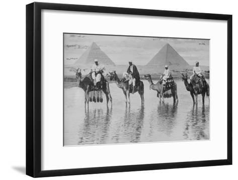 Camels with Native Riders on Board Stand in Reflective Floodwaters--Framed Art Print