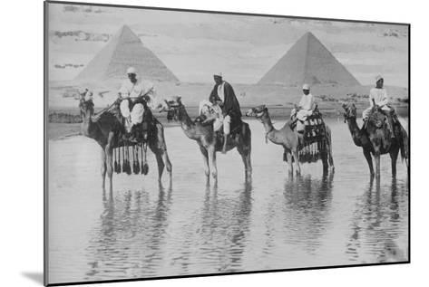 Camels with Native Riders on Board Stand in Reflective Floodwaters--Mounted Art Print