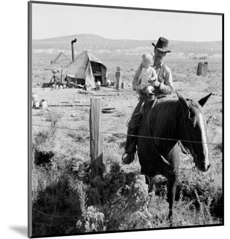 Cowboy Holds His Baby While Riding a Horse-Dorothea Lange-Mounted Art Print