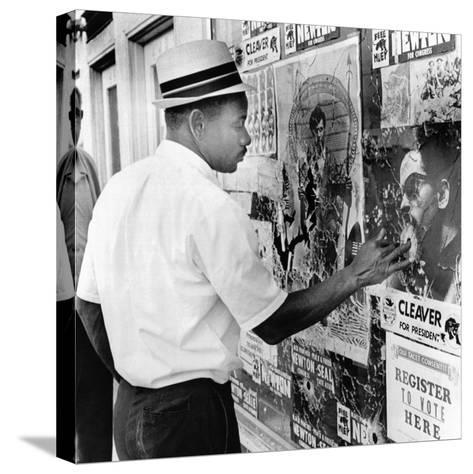 An African American Pokes His Finger into a Bullet Hole in the Oakland Black Panther's Headquarters--Stretched Canvas Print