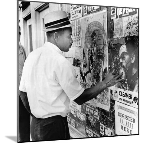 An African American Pokes His Finger into a Bullet Hole in the Oakland Black Panther's Headquarters--Mounted Photo