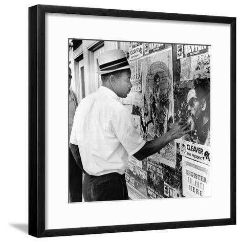 An African American Pokes His Finger into a Bullet Hole in the Oakland Black Panther's Headquarters--Framed Art Print