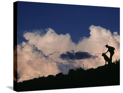 A Hiker and Her Dog Below Thunderheads in Arid Volcanic Tablelands-Gordon Wiltsie-Stretched Canvas Print