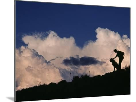 A Hiker and Her Dog Below Thunderheads in Arid Volcanic Tablelands-Gordon Wiltsie-Mounted Photographic Print