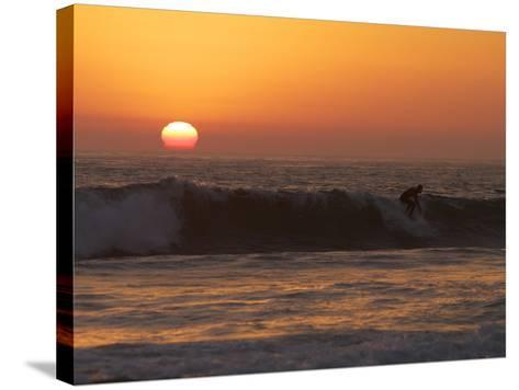 Surfer Riding a Wave at Sunset over the Pacific Ocean-Tim Laman-Stretched Canvas Print
