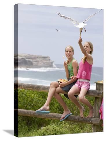 Two Girls Feeding Chips to a Seagull at the Beach-Louise Hammond-Stretched Canvas Print