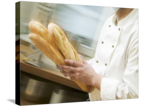 Chef Hurrying Through Kitchen with Baguettes--Stretched Canvas Print