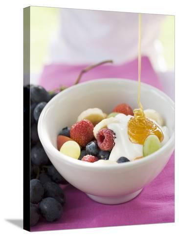 Honey Running onto Fruit Muesli with Yoghurt--Stretched Canvas Print