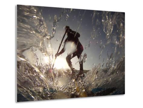 A Stand Up Paddleboarder Surfs a Wave Near Nags Head Pier-Skip Brown-Metal Print
