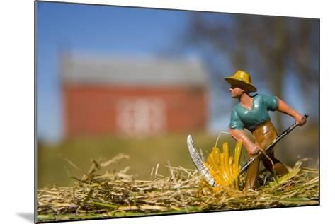 A Lead Figurine of a Farmer Cutting Hay with a Real Barn in Distance-Stephen St^ John-Mounted Photographic Print