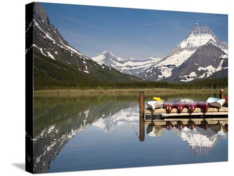 Colorful Canoes Line the Dock at Many Glacier Lodge on Swiftcurrent Lake During Sunrise-Brad Beck-Stretched Canvas Print