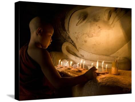 A Novice Monk Lighting Candles at a Massive Buddha Statue in Burma (Myanmar)-Kyle Hammons-Stretched Canvas Print