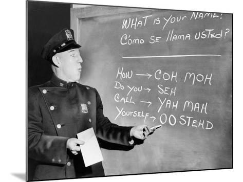NYC Police Officer Practices Basic Spanish Phrases Written on Blackboard, Ca. 1955--Mounted Photo