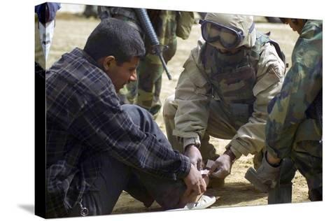 Iraqi Detainee Receives a Bandage While under Interrogation, March 24, 2003--Stretched Canvas Print