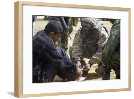 Iraqi Detainee Receives a Bandage While under Interrogation, March 24, 2003--Framed Art Print