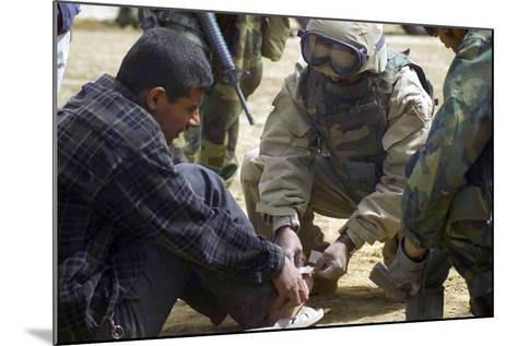 Iraqi Detainee Receives a Bandage While under Interrogation, March 24, 2003--Mounted Photo