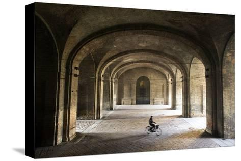 A Bicyclist Passes Through Archways in Palazzo Della Pilotta-Dave Yoder-Stretched Canvas Print