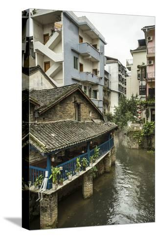 A Restaurant and Apartments Rise Above a River in Yangshuo, China-Jonathan Kingston-Stretched Canvas Print