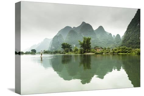 A Barefoot Man Walks Across the Li River Near Yangshuo, China-Jonathan Kingston-Stretched Canvas Print