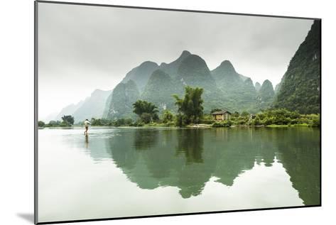 A Barefoot Man Walks Across the Li River Near Yangshuo, China-Jonathan Kingston-Mounted Photographic Print