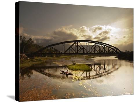 Sunset Over a Bridge in Da Nang with a Small Fisherman's Boat-Alex Saberi-Stretched Canvas Print