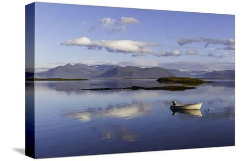 A Johnboat with An Outboard Motor and Its Reflection in Calm Blue Water-Jonathan Irish-Stretched Canvas Print