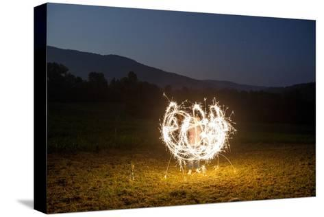 A Child Plays with Sparklers in a  Field in Lost Cove, Tennessee-Stephen Alvarez-Stretched Canvas Print