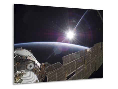 The International Space Station Backdropped by the Bright Sun Over Earth's Horizon-Stocktrek Images-Metal Print