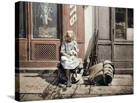 A Little Girl Playing with Her Doll; Two Guns and a Knapsack are Next to Her on the Ground, Reims,…-Fernand Cuville-Stretched Canvas Print