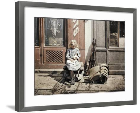 A Little Girl Playing with Her Doll; Two Guns and a Knapsack are Next to Her on the Ground, Reims,…-Fernand Cuville-Framed Art Print
