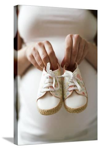 Pregnant Woman Holding Baby Shoes-Ian Boddy-Stretched Canvas Print